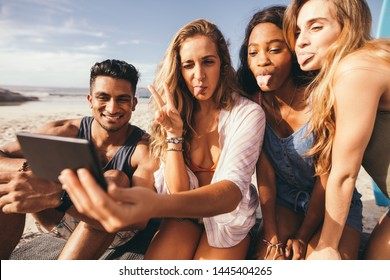 Close up of group of friends at the beach taking selfie using mobile phone. Cheerful friends on vacation making faces sticking their tongue out while taking selfie.