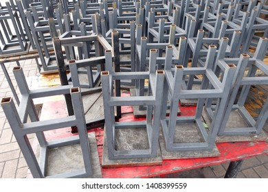 close up group of gray metal stool with wooden seats placed on red wooden table of outdoor restaurant after service is closed, concept sluggish economy causes food and beverage business closing down