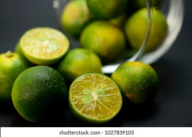 close up of group green calamansi lime on black background