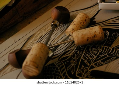 close up of a group of linocutting tools over some lino artwork in an artists studio