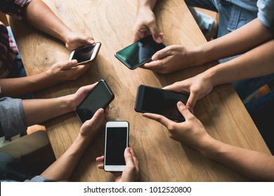 Close up group of many people using smart phone together on wood table. Technology or business communication concept.