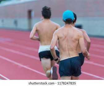 A close up of a group of men viewed from the back are running