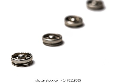 Close up of a group of metal Snap on Buttons on white background. Macro Photography