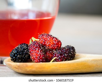 Close up group of mulberries is placed on a wooden spoon in front of a glass of mulberries water. Mulberry this a fruit and can be eaten and delicious and sweet nature. Copy Space