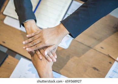 Close up group of peoples joining hands on top for starting joint business, common goal, successful team building, motivated enthusiastic co-workers starting work on project, running company together