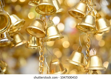 Close up group of shiny golden small bells with blur bokeh background, selective focus