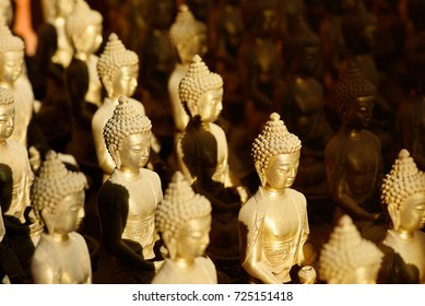 Close Up group of small buddha brass sculpture with light and shadow, selective focus.