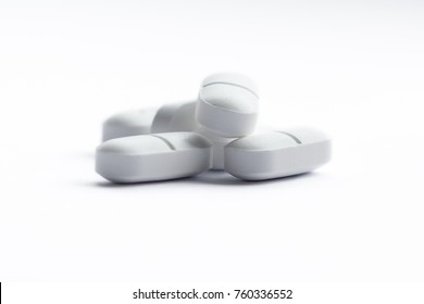 close up of a group of white tablets isolated on a white background