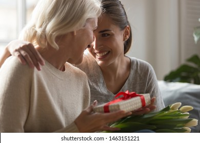 Close up grown up loving daughter congratulates eight march or international women day middle aged mother giving her gift box spring flowers white tulips, life events, attention love and care concept
