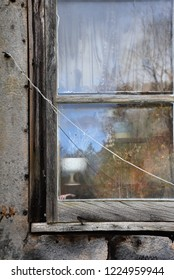 Close up of gruesome rotted out grungy window of haunted abandoned house. Dead plant and hand seen though the window.