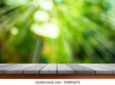 Close up grunge rustic green wooden table top shallow dept of field with sunlight ray of blurred fresh green nature background for products display.