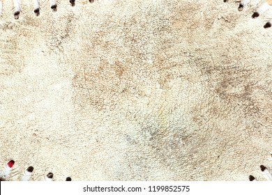 Close up of the grungy leather texture of a used baseball