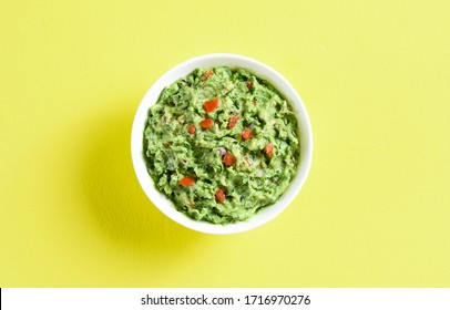 Close up of guacamole dip in bowl over yellow background with free text space. Healthy avocado spread. Top view, flat lay