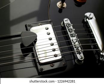 close up guitar pick and  black vintage electric jazz guitar