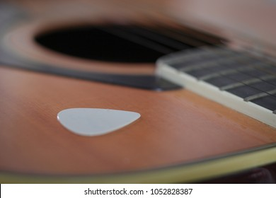 Close up of guitar pick on body of guitar