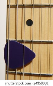 Close up of Guitar Pick on a Fret Board
