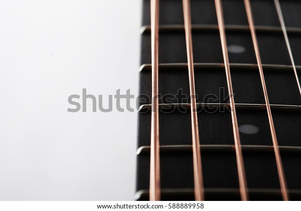 close up of guitar strings and fret board on white background