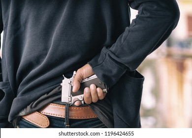 Close up gun in man's hand tucked at the back jeans.