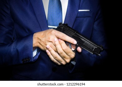 Close up of gunman in business man suit holding pistol in hands.
