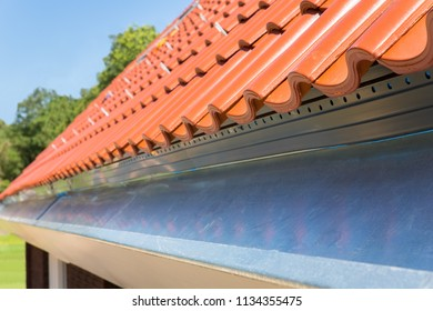 Close up gutter with roof tiles at new house