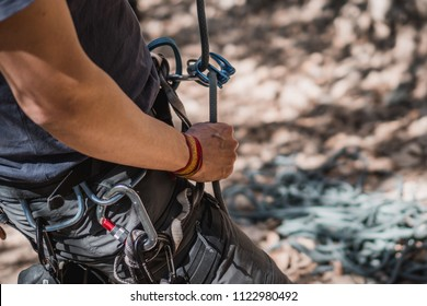 Close up a a guy belaying in a rock climbing route using an atc and a rope