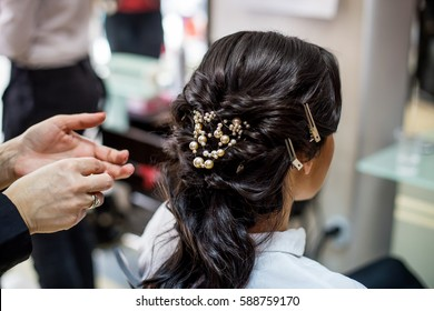 Close up of hair stylist making a braid on long brunette hair in a beauty salon. Bridal hairstyle. Wedding