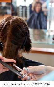 Close up of hairdresser giving a haircut to female customer at parlor
