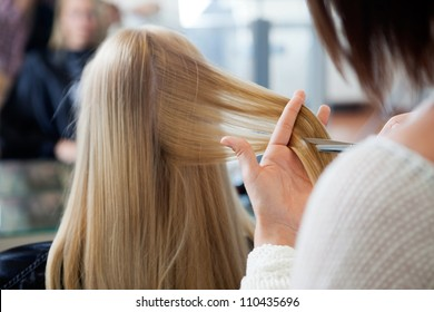 Close up of hairdresser giving a new haircut to female customer at parlor