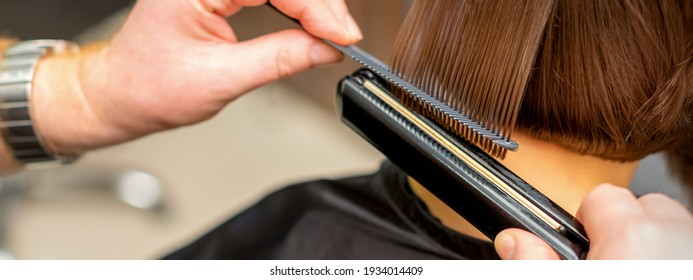 Close up of the hairdresser straightening the short hair of a female client with a hair straightening iron in a beauty salon. Selective focus