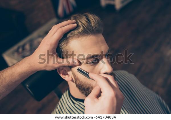 Nahaufnahme eines Friseurwerkes für einen attraktiven jungen Blond im Friseur. Er stylt seinen Bart und rasiert ihn mit geraden Rasierapparaten