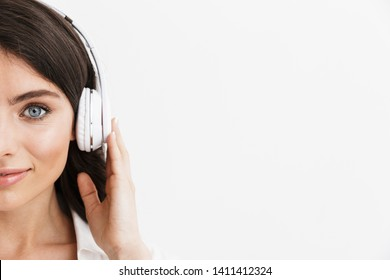 Close up half face of a beautiful young woman with long curly brunette hair wearing white shirt standing isolated over white background, enjoying listening to music with headphones