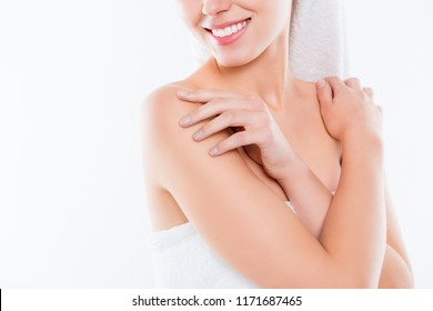 Close up half face cropped portrait of smiling woman's crossed hands touching shoulders enjoying smooth skin after cream shower isolated on white background