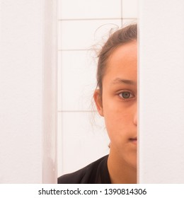 Close up half face portrait teenager girl looking through white metal bars, self-awareness and self worth concept, square image