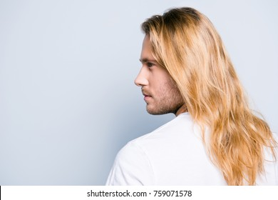 Close up half turned side view photo of young stylish handsome man with bristle and long smooth blond hair, isolated on grey background