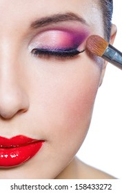 Close up of half-face of girl with brush applying bright pink makeup on eye, isolated on white