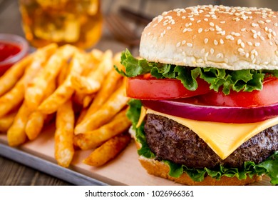 Close up of hamburger with onions, lettuce, tomato on a sesame seed bun with seasoned french fries and ketchup and  glass of iced tea
