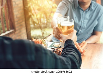 Close up of hand adult man holding beer glass and clinking together.