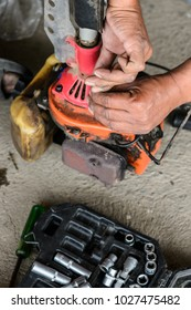 Close up hand of agriculture repairing old brush cutter with tools on cement floor