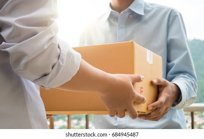 Close up hand of asia woman are receive a box from delivery man with sun light in delivery service concept