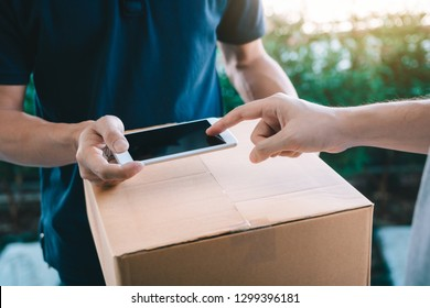 Close up of hand asian man using smartphone pressing screen to sign for delivery from the courier at home.