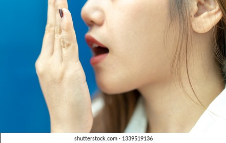 Close up hand of Asian woman doing a breath test. young girl checking her breath with hand or open mouth Unrecognizable. Health Care and medical concept