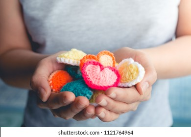 close up hand of asian woman holding heart, made from crocheted