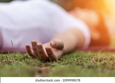 Close up hand of Asian woman practice yoga Dead Body pose or Savasana pose lying on green grass for yoga Meditation feeling so relax and comfortable,Healthcare Concept