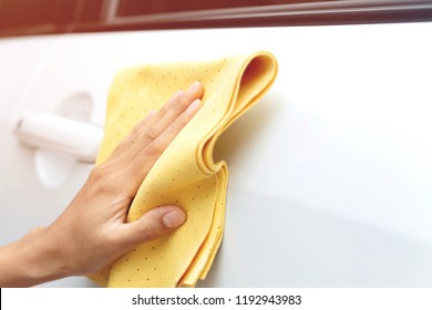 close up hand auto service staff cleaning white car Worker with microfiber cloth Car detailing series , car wash or car detailing and valeting concept