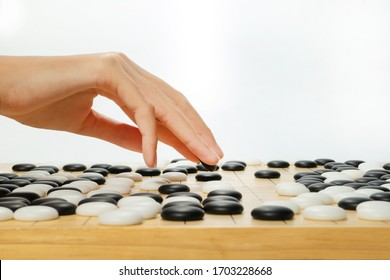 close up hand with baduk black stone on the board game - Chinese, Japan, Korean board game GO with black and white stone. Go or wei-Chi - WeiQi traditional asian board game