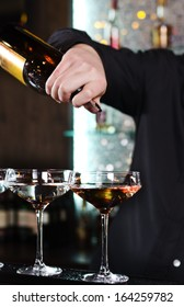 Close up of the hand of a bartender mixing alcoholic cocktails pouring from a bottle into an elegant cocktail glass on a bar counter