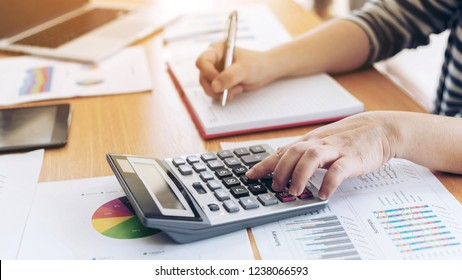 close up hand of business employee accountant with calculator calculating annual income tax and company income calculation - business concept