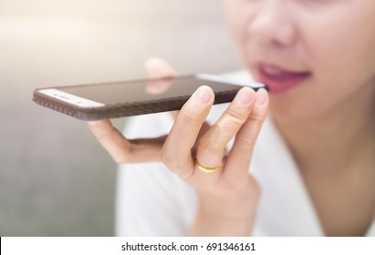 Close up of hand business girl using a smart phone voice recognition with a warm light background.