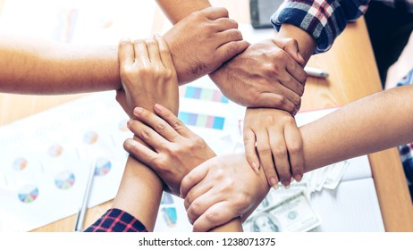 close up hand of business partnerships people crossed hands  finishing up meeting showing unity over office desk , business partner teamwork concept