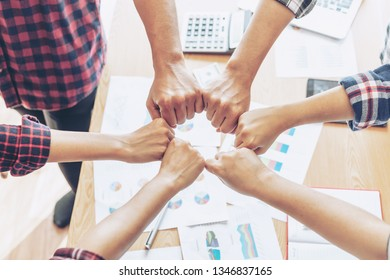 close up hand of business partnerships people bump hands finishing up meeting showing unity over office desk , business teamwork concept